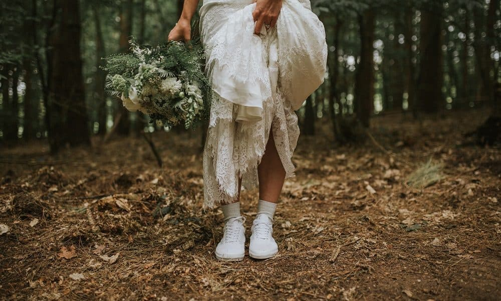 Photo of bride in a forest showing her white sneakers