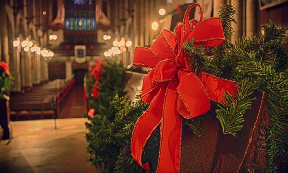 Close up of a church pew decorated with a red Christmas bow.