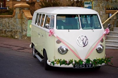 Gorgeous white VW wedding campervan decorated with pink ribbons and floral garland.