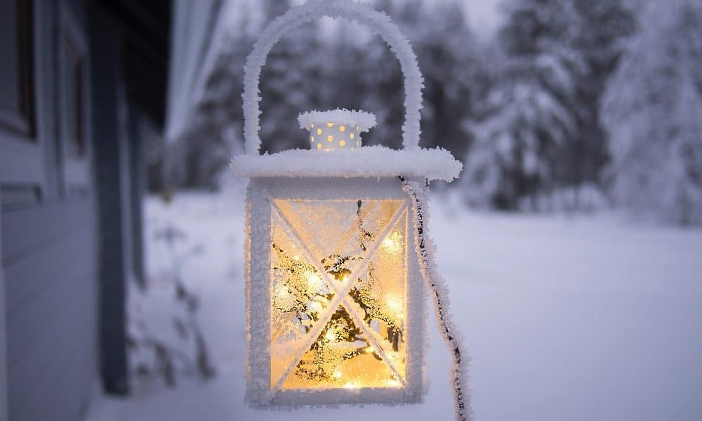 Whiter lantern covered in snow with fairy lights inside.