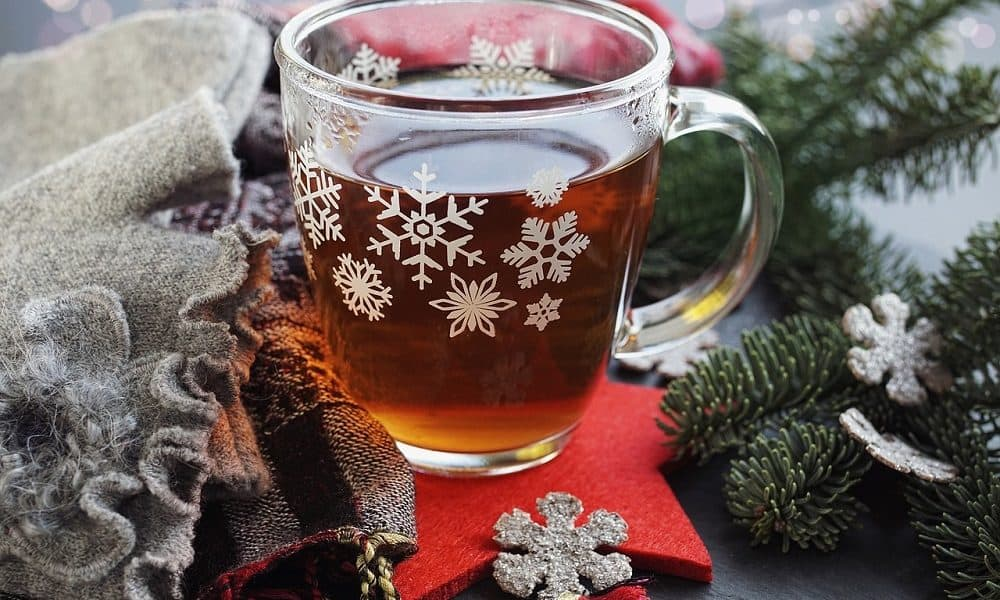 Mulled cider in a glass mug decorated with snowflakes.