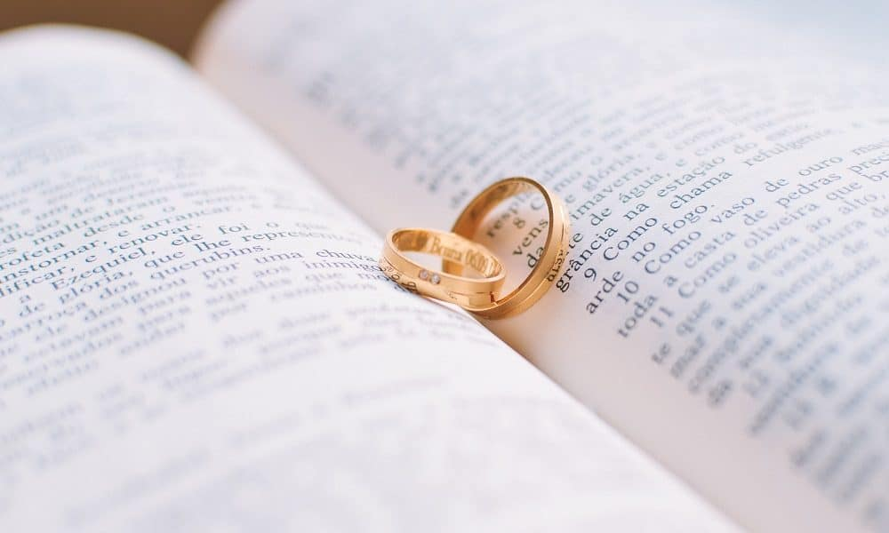 An open bible holding two gold wedding rings.