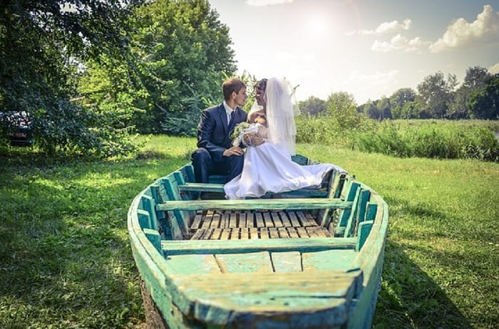 A recently married couple sit in a rustic looking rowing boat (turquoise) parked on dry land, surrounded by greenery.