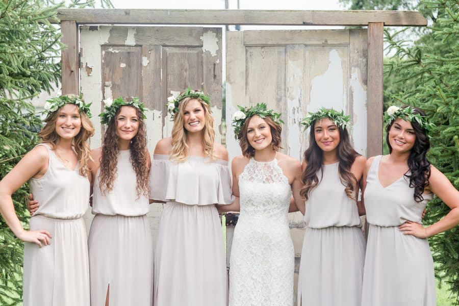 Bride and bridesmaids in pastel color dresses and crowns made of foliage.