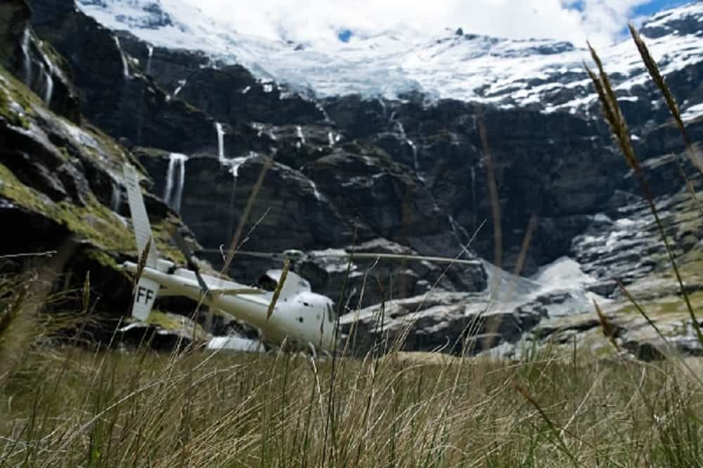 White helicopter lands in a mountainous valley surrounded by green grass.