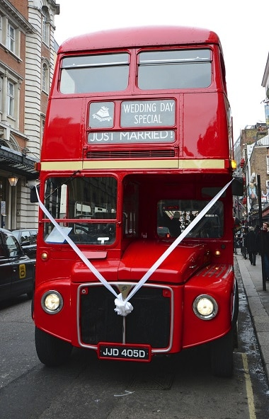 Red London wedding bus, decorated with white ribbons.