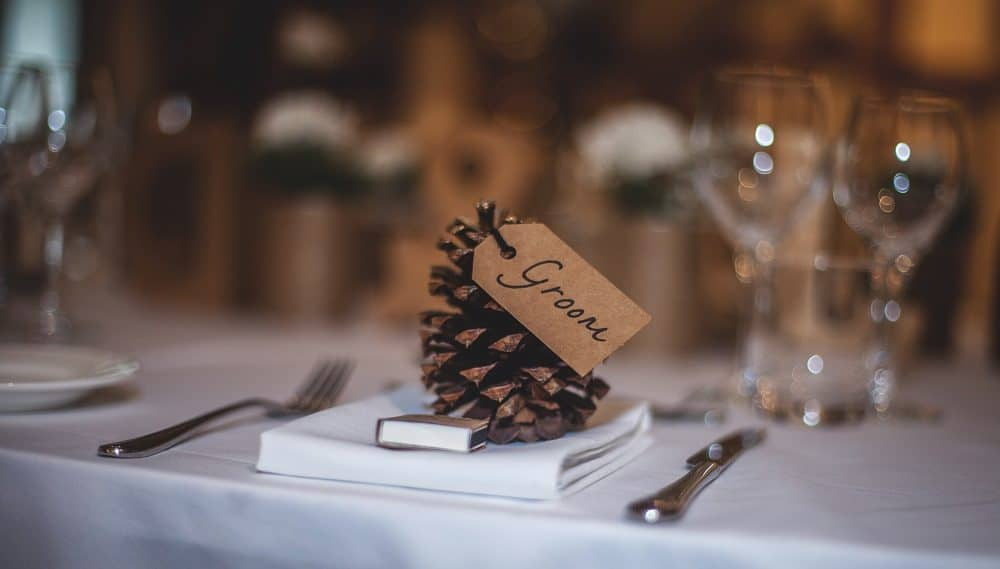 Pinecone wedding table decoration with brown groom tag.