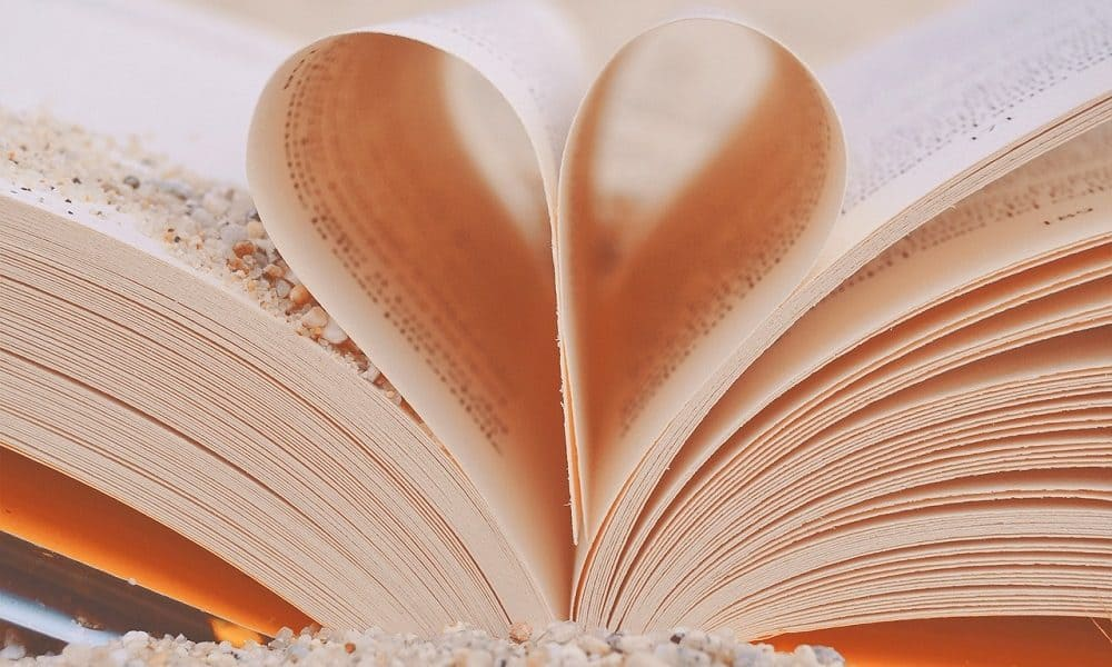 An open book with two pages folded to form a heart