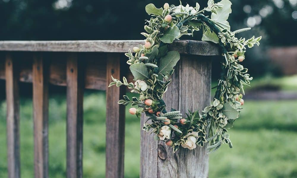 Rustic wreath hanging on a wooden bench.