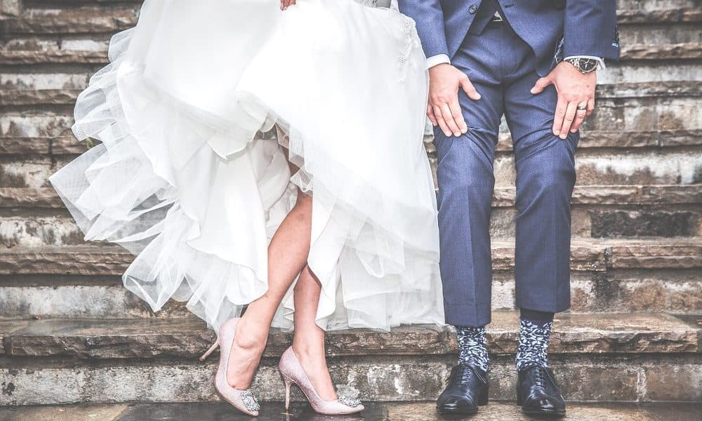 A recently married couple show off their footwear under their wedding clothes.