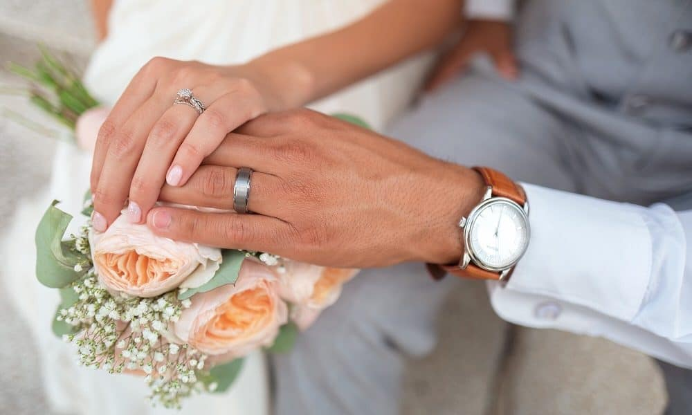A recently married couple hold hands on top of a poesy of roses.