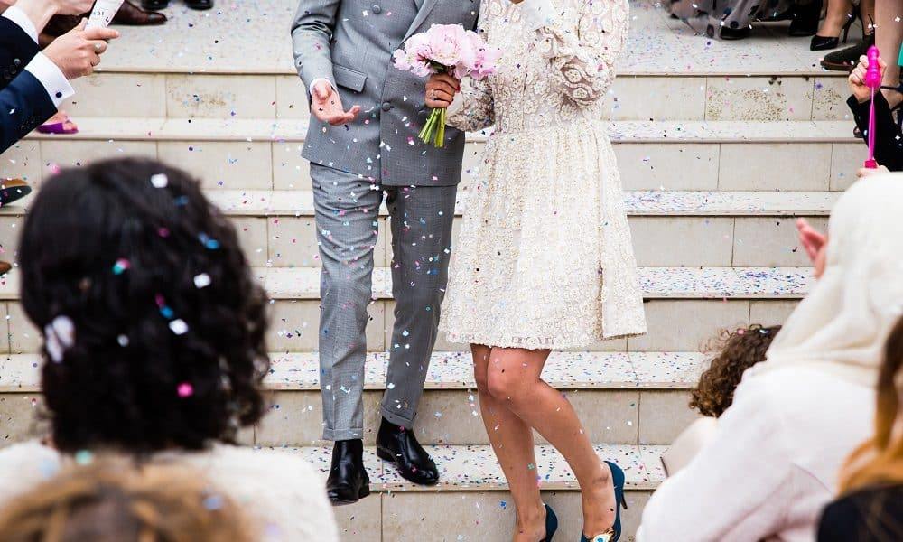 Recently married couple have confetti thrown on them.