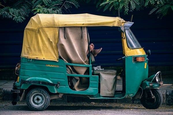 Tuk tuk with a turquoise body and yellow roof.