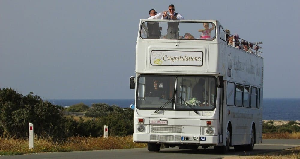 White open-top double decker wedding bus on the road.
