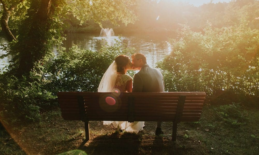 Married couple kissing on a bench during sunset.
