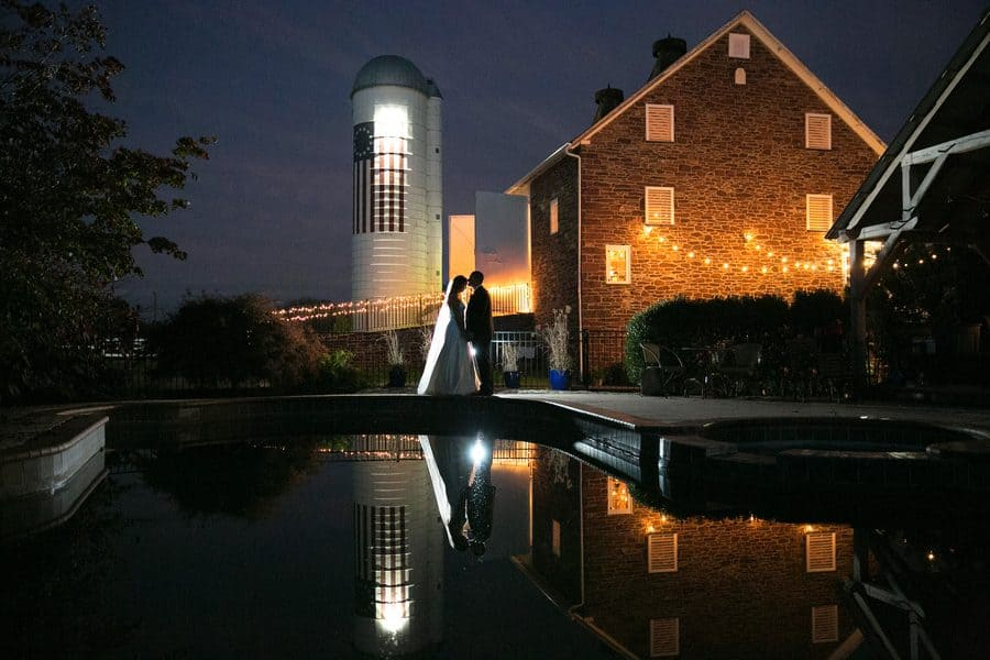 The Durham Hill Barn and silo, with the bride and groom reflected in the pool.