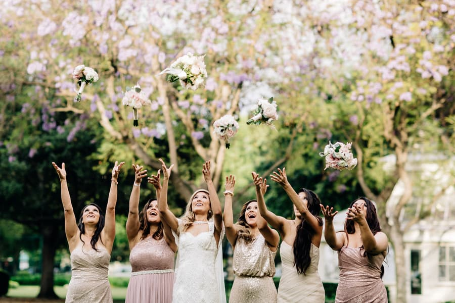 bridesmaids throwing boquets in the air